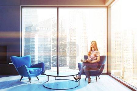 Foto de Mujer bonita en un loft interior de la sala de estar con un suelo de madera una chimenea negra y dos sillones azules cerca de una mesa de café. 3d representación maqueta de imagen tonificada - Imagen libre de derechos