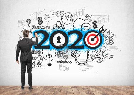 Photo pour Vue arrière d'un jeune homme d'affaires dessinant une esquisse de stratégie d'entreprise 2020 sur un mur en béton. Concept de nouvelle année et de planification - image libre de droit