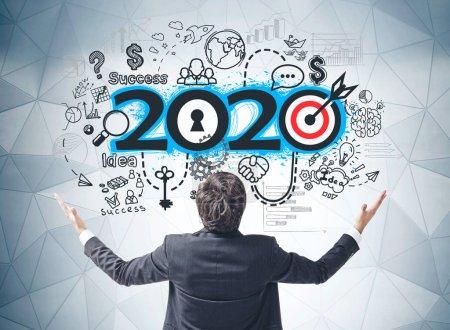 Photo pour Vue arrière du jeune homme d'affaires heureux attendant l'année 2020 debout près du mur gris avec un croquis coloré dessiné dessus. Concept de résolutions et de planification pour la nouvelle année - image libre de droit
