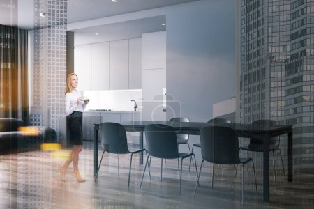 Photo pour Smiling blonde woman standing in modern dining room with gray walls, wooden floor, comfortable table with chairs, sofa and kitchen in background. Double exposition de l'image tonique - image libre de droit