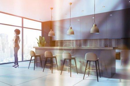 Photo pour Jeune Afro-Américaine debout dans une cuisine panoramique élégante avec des murs noirs et en bois, des comptoirs gris et un bar avec tabourets. Image tonique - image libre de droit