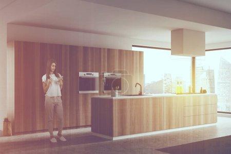 Photo pour Jeune femme avec café debout dans le coin cuisine avec murs blancs, plancher de béton, île en bois avec évier et cuisinière intégrés et deux poêles. Double exposition de l'image tonique - image libre de droit