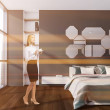 Blonde young woman standing in stylish bedroom wit...