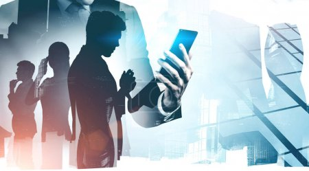 Photo for Unrecognizable manager looking at smartphone standing in Moscow city with double exposure of his colleagues. Concept of leadership and brainstorming. Toned image - Royalty Free Image