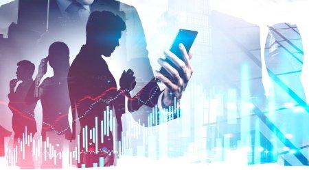 Photo pour Homme d'affaires avec smartphone et ses collègues travaillant ensemble dans la ville de Moscou avec double exposition de tableau financier flou. Concept d'analyse de marché et de travail en équipe. Image tonique - image libre de droit