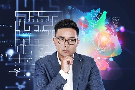 Photo pour Jeune homme d'affaires asiatique sérieux dans des lunettes sur fond sombre avec un croquis créatif et analytique coloré. Concept de développement et de brainstorming. Image tonique - image libre de droit