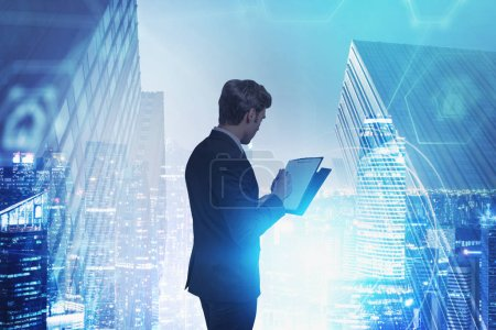 Photo for Young businessman with clipboard standing in blurry night city with double exposure of immersive digital interface. Concept of internet of things and big data. Toned image - Royalty Free Image