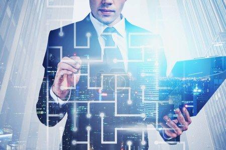 Photo pour Jeune homme d'affaires méconnaissable travaillant avec un labyrinthe numérique dans une ville nocturne. Concept des tâches et de la technologie stimulantes. Double exposition de l'image tonique - image libre de droit