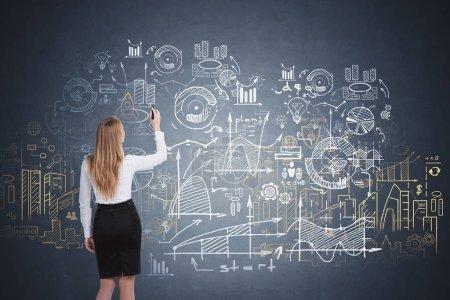 Foto de Vista trasera de la mujer de negocios rubia dibujo creativo inicio boceto en pizarra. Concepto de educación empresarial. Doble exposición - Imagen libre de derechos
