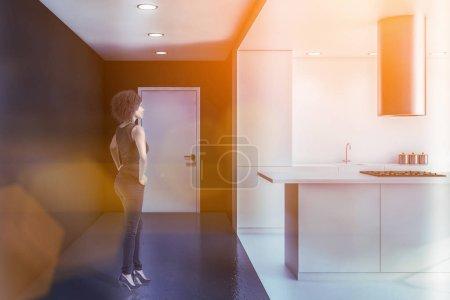 Photo pour Jeune Afro-Américaine debout dans une cuisine moderne avec des murs gris et blancs, un plancher de béton, des comptoirs blancs et une île blanche avec cuisinière intégrée. Image tonique - image libre de droit
