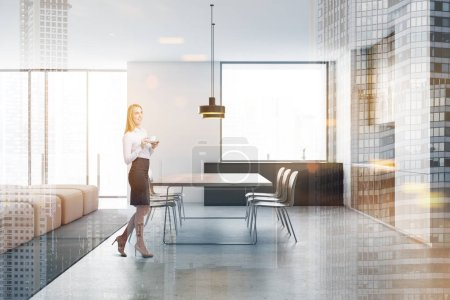 Photo pour Smiling blonde woman standing in modern kitchen with white walls, gray and wooden countertops, dining table and comfortable beige sofa. Double exposition de l'image tonique - image libre de droit