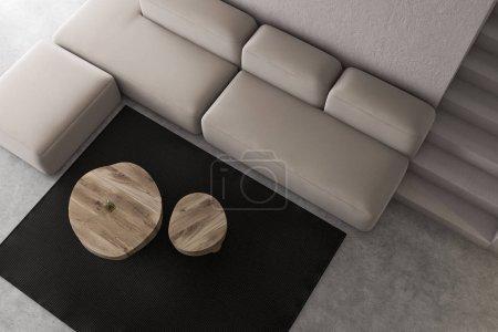 Photo pour Vue de haut de l'élégant salon aux murs blancs rudimentaires, sol en béton, canapé confortable près des tables rondes et escaliers menant au deuxième étage. 3d Rendu - image libre de droit