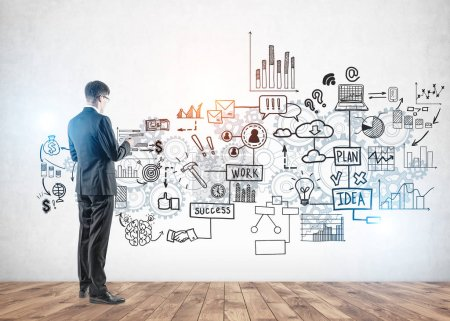 Photo pour Side view of young business man with glasses and document looking at creative business strategy sketch drawn on concrete wall. - image libre de droit