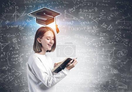 Photo pour Joyeux jeune étudiant en vêtements décontractés tenant livre de copie ouverte dans sa main debout près du tableau noir avec formule et chapeau de graduation. Concept de science et de carrière - image libre de droit