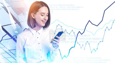 Photo for Smiling young businesswoman with smartphone standing in abstract city with double exposure of digital graphs. Concept of investment and hi tech in market analysis. Toned image - Royalty Free Image