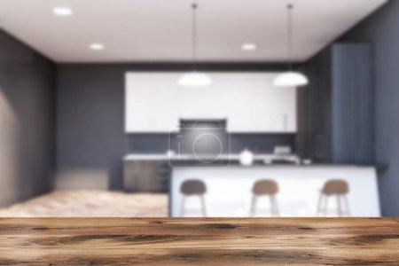 Photo pour Table pour vos produits dans une cuisine moderne floue avec murs gris, parquet, placards blancs, comptoirs gris avec évier et cuisinière intégré et confortable bar blanc avec tabourets. 3d Rendu - image libre de droit