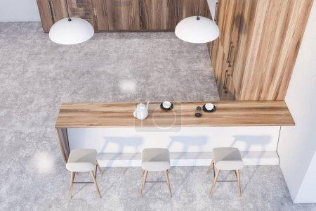 Photo pour Vue en haut de la cuisine moderne avec murs blancs, plancher de béton, comptoirs et placards en bois et confortable bar blanc avec tabourets et lampes de style industriel. 3d Rendu - image libre de droit