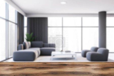 Photo pour Table pour votre produit dans un salon panoramique flou avec des murs gris, sol en bois, canapé gris confortable et fauteuils debout près de la table de style japonais blanc. Rendu 3d - image libre de droit