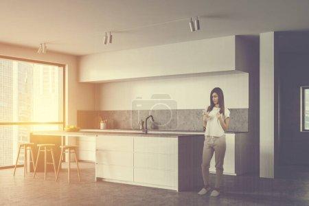 Photo pour Jeune femme avec café debout dans une cuisine ensoleillée avec murs blancs, sol en béton, comptoirs blancs, bar avec tabourets et fenêtre avec paysage urbain. Double exposition de l'image tonique - image libre de droit