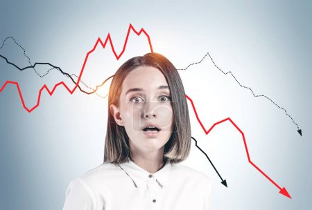 Photo for Desperate frightened young woman in formal clothes standing near gray wall with falling graphs. Concept of financial crisis and loss - Royalty Free Image