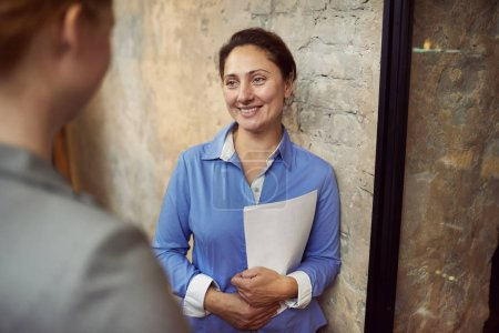 Photo for Mature businesswoman holding documents in hands and smiling to partner while standing in the corridor - Royalty Free Image