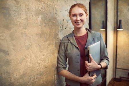 Photo pour Portrait de jeune employé de bureau tenant un ordinateur portable dans les mains et souriant à la caméra dans un bureau moderne - image libre de droit