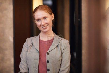 Foto de Retrato de la joven empresaria pelirroja sonriendo a la cámara mientras está de pie en la oficina del pasillo - Imagen libre de derechos