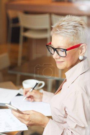 Photo pour Femme d'affaires mature sérieuse avec des lunettes regardant le téléphone portable et prenant des notes dans le document à la table au bureau - image libre de droit