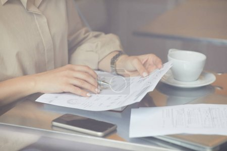 Photo for Close-up of young woman sitting at the table with cup of coffee and mobile phone and reading business document - Royalty Free Image