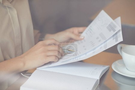 Photo for Close-up of young manager examining financial report while sitting at the table with cup of coffee in cafe - Royalty Free Image