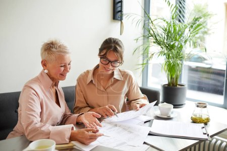 Photo for Young businesswoman in eyeglasses sitting at the table together with mature businesswoman reading and discussing documents together - Royalty Free Image