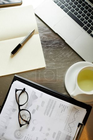 Photo for High angle view of documents with financial charts cup of tea and laptop on the table - Royalty Free Image