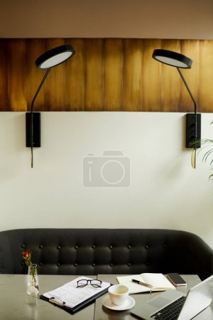 Photo for Workplace with laptop computer and documents with modern lamps above the table at office - Royalty Free Image