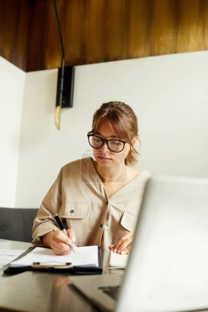 Photo for Concentrated young businesswoman wearing eyeglasses sitting at the table in front of laptop and signing document - Royalty Free Image
