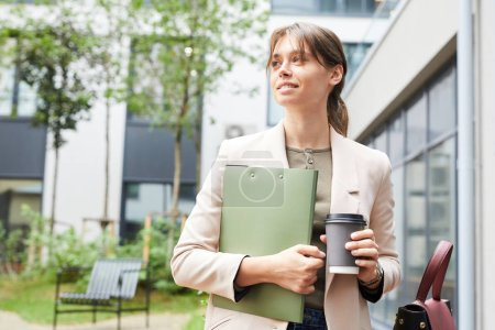 Photo for Young businesswoman holding folder and disposable cup of coffee in hands and walking outdoors in the city - Royalty Free Image
