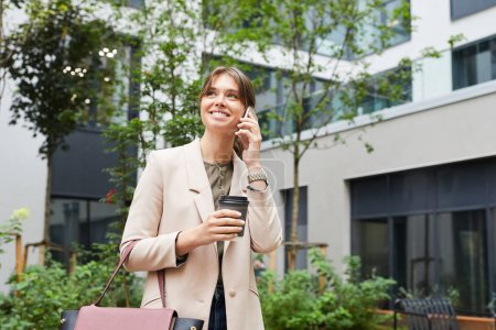 Photo for Young smiling businesswoman talking on the phone and drinking coffee from disposable cup while walking along the street in the city - Royalty Free Image