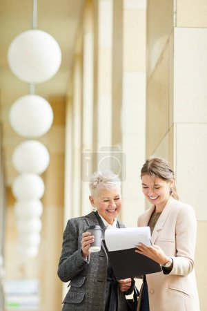 Photo for Young businesswoman and mature businesswoman reading document together and smiling while standing outdoors - Royalty Free Image