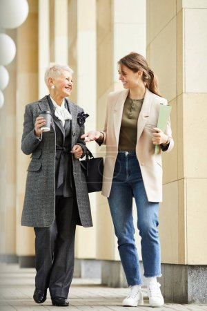 Photo for Two happy women in elegant clothing talking and laughing while walking along the street outdoors - Royalty Free Image