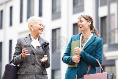 Photo for Two successful businesswomen talking while walking along the street in the city - Royalty Free Image