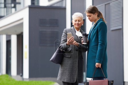 Photo for Mature woman showing something on mobile phone to friend while meeting in the city - Royalty Free Image