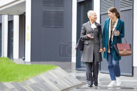 Photo for Two friends in elegant stylish clothing walking together along the street and drinking coffee - Royalty Free Image