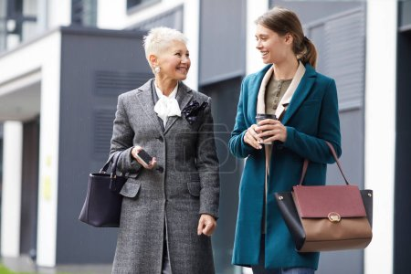 Photo for Happy mother in elegant coat smiling to daughter while walking along the street in the city - Royalty Free Image