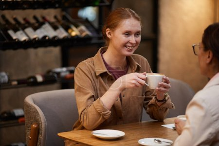 Photo for Smiling young woman on meeting with friend in cafe drinking coffee and talking - Royalty Free Image