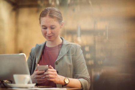 Photo for Young businesswoman using mobile phone while sitting at the table in front of laptop computer in cafe - Royalty Free Image