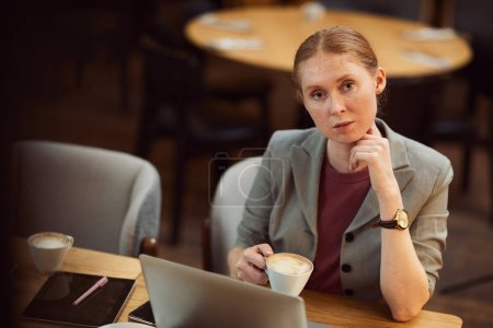 Photo for Portrait of young businesswoman drinking coffee and looking at camera while working at the table with laptop in the restaurant - Royalty Free Image