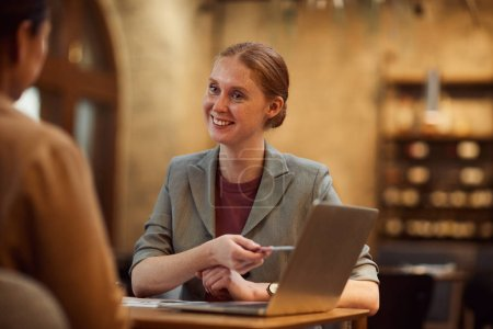 Photo for Young businesswoman smiling and pointing at laptop discussing online presentation with colleague in cafe - Royalty Free Image