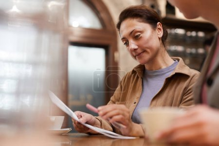 Photo for Mature woman sitting at the table and reading business contract together with colleague - Royalty Free Image