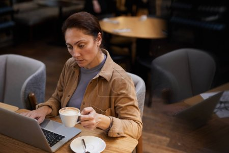 Photo for Serious mature businesswoman holding cup of coffee and typing on laptop computer while sitting at the table in cafe - Royalty Free Image