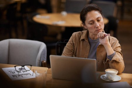 Photo for Serious businesswoman concentrating on online work working on laptop at the table with financial graphs and coffee cup in cafe - Royalty Free Image