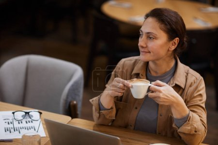 Photo for Mature woman drinking coffee while sitting at the table and working on laptop with documents in coffee shop - Royalty Free Image